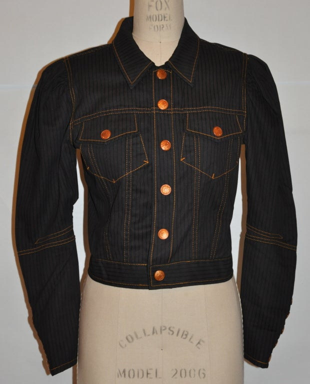 """Jean Paul Gaultier's """"Haute Jeanerie"""" Black cotton denim jacket has detailing top-stitching. There are six (6) front snap closures and also seven (7) snaps detailing on the sleeve's cuff. There are two breast patch pockets on front. On the back  the"""