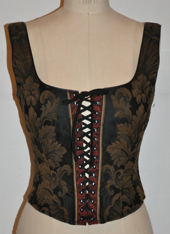 """Gigi Clark bustier has adjustable lace-up in the front and the back has nine hook-n-eyes in the back. The edges have black leather piping along the neckline and armhole.   Underarm circumference is 32"""", underarm-to-hem is 9""""."""