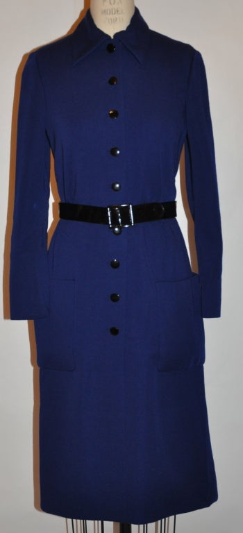 Norman Norell Navy knit dress has nine buttons in front along with an extra button still in its original envelope. The dress comes with its own patent leather belt and is fully lined in silk of the same navy hue. The front measures 40