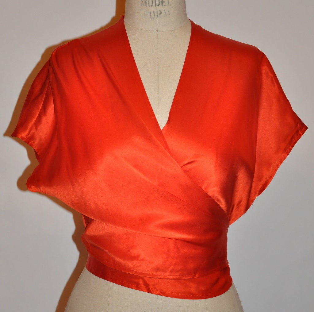 "Guy Laroche couture red silk crepe de chine wrap-around blouse measures 17"" in length. The underarm circumference measures 44"" (Because of the wrap front, it can be extended and adjusted). The neck-to-shoulder measures 12"", circumference is 14"". The"