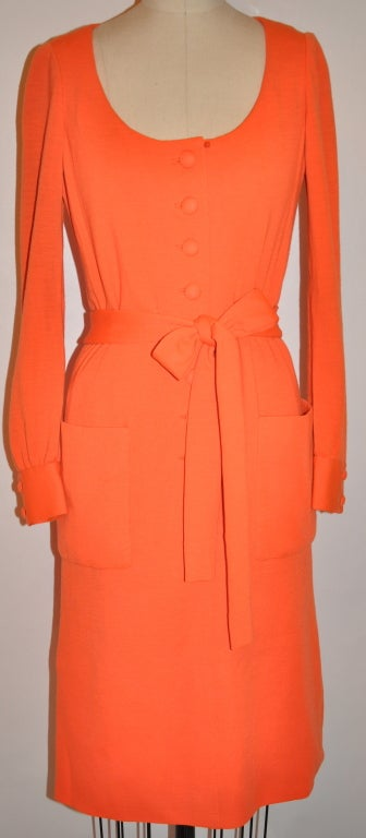 This wonderful timeless Iconic Norman Norell fully lined dress is in a neon tangerine hue. The lining is in silk of the same hue. The dress has a attached self-tie belt which measures 79 inches x 2 inches. There are two patch pockets on front.    As