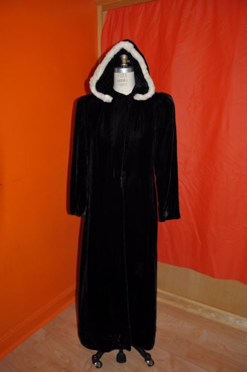 Victorian floor length velvet hooded evening coat with mink trim. This wonderful soft velvet evening coat is trimmed with white mink along the edge on the hood. The coat has deep domain sleeves tapering  to a fitted cuff. The coat is lined in winter