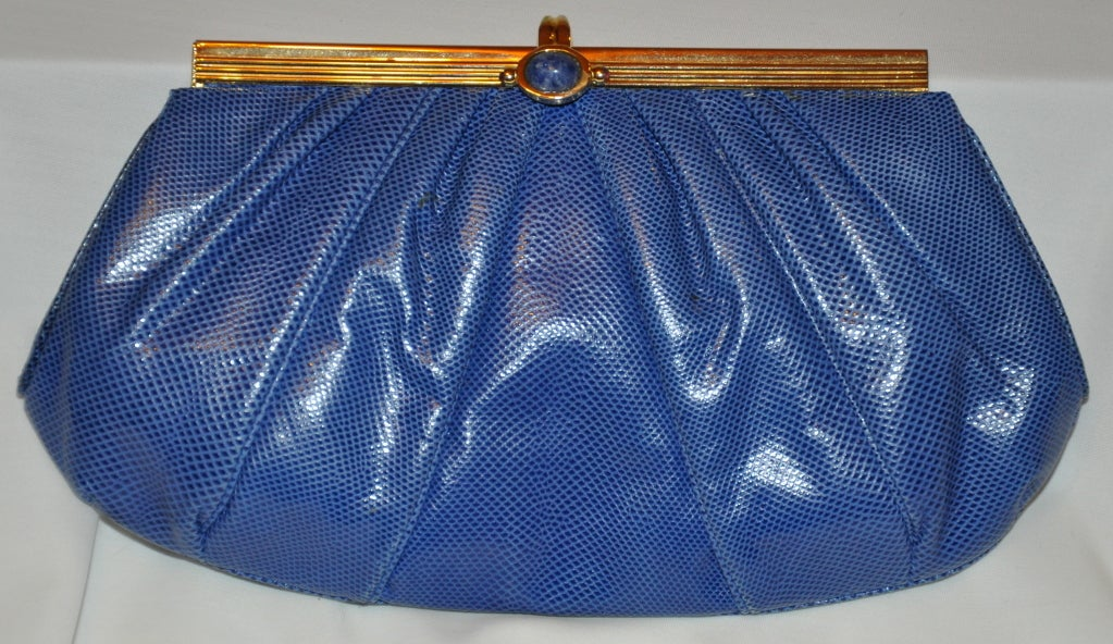 Judith Leiber blue lizard clutch has a gold metal frame and highlighted with Lapis at the center.   The width measures 6 3/4