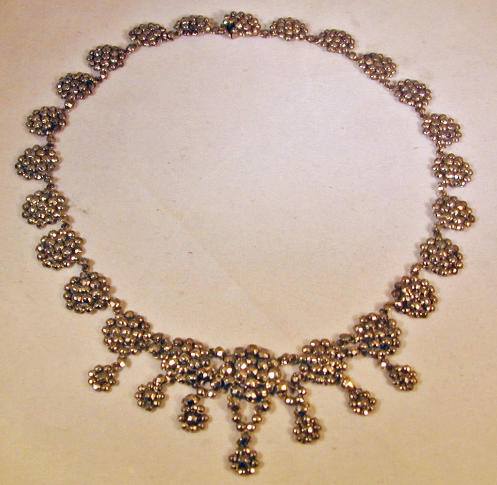 Elegant round plaques of cut steel embellish this collar, wearable day or night. Cut steel jewelry is said to have started in Woodstock, England where it evolved from the craft of constructing steel toys. It became popular as an alternative to