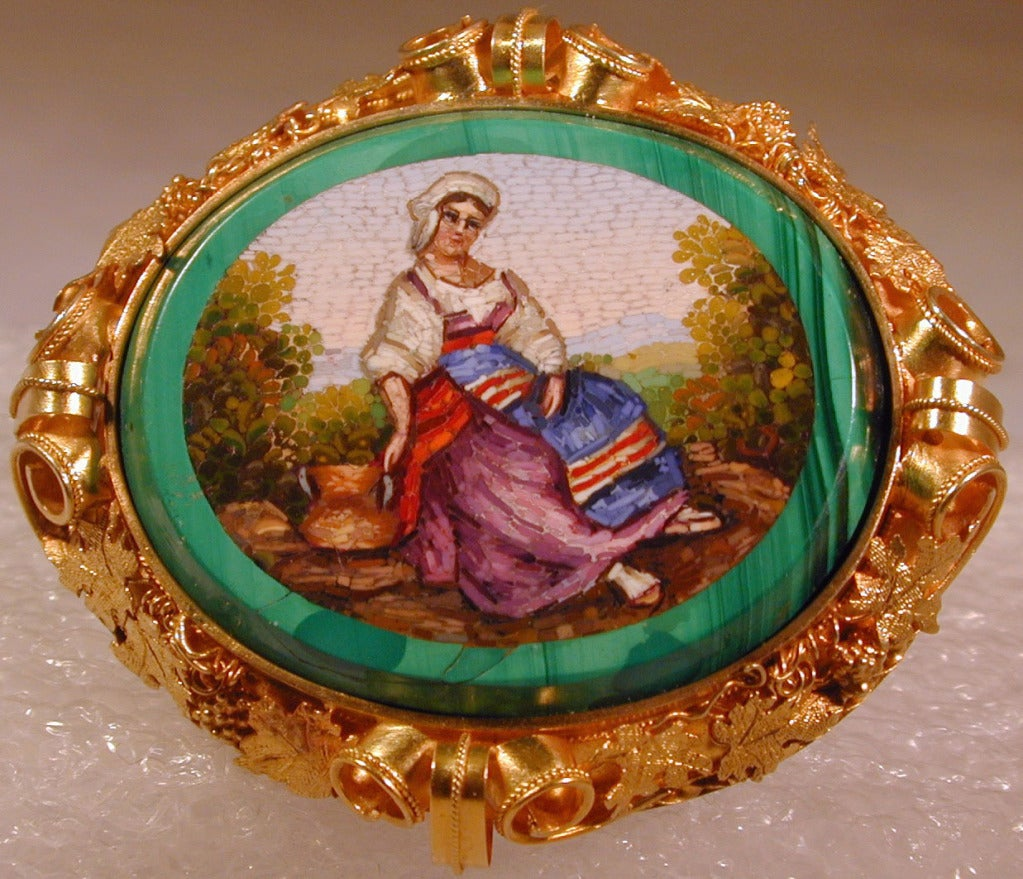 Colorful depiction of a peasant girl graces this micromosaic brooch purchased during the Grand Tour and brought back to England to be set in an elaborate 18K bezel decorated with grapes and leaves. The glass tesserae are set in malachite.