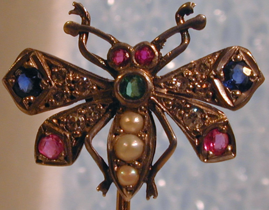 Fluttering gem set butterfly stickpin will brighten any lapel or scarf. Set with rose diamonds, rubies, sapphires, pearls and an emerald this bright beauty will liven up your day. The pin is 2