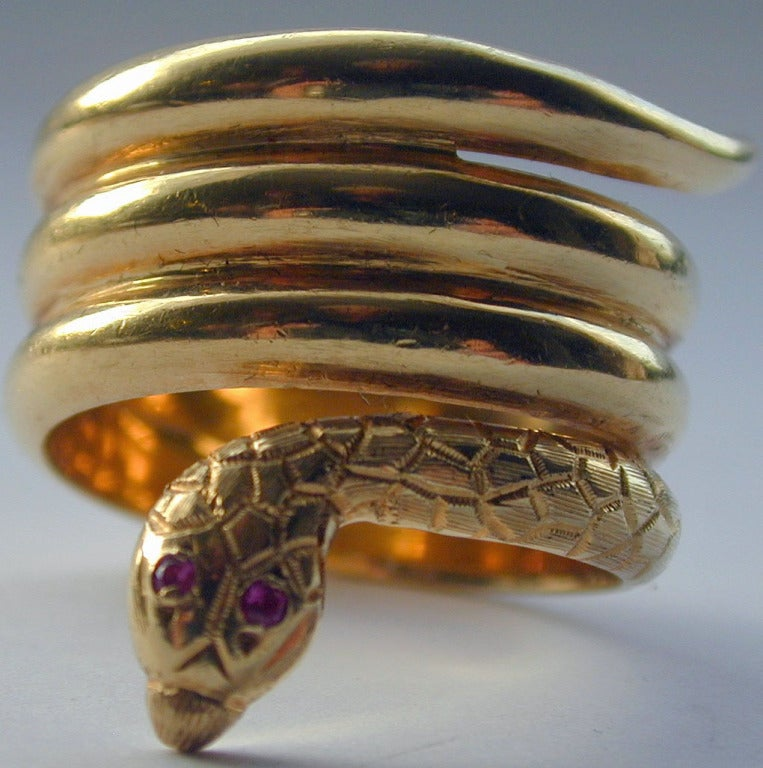 Beautifully engraved wide 18K gold snake ring with ruby eyes will make a wonderful statement but never bite. Snake rings became popular in England after Queen Victoria received one as her engagement ring. The ring is size 11 1/4 and measures 1