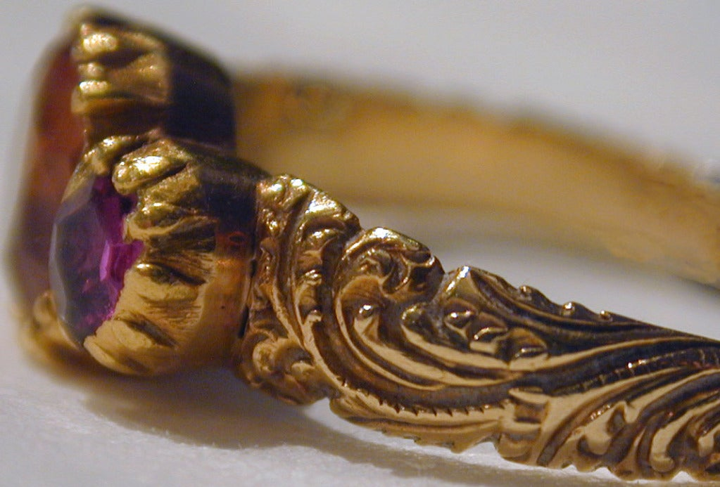 Georgian topaz ring flanked by two rubies in a carved 18K yellow gold setting will enliven your hand worn alone or stacked with other rings. The ring is a size 7 1/2.