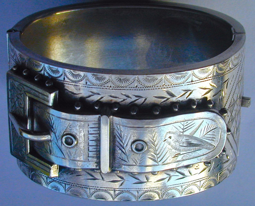 Victorian sterling silver buckle motif cuff bracelet is engraved with arches and foliate designs and a charming bird on the flap of the strap. The bracelet measures 1 1/2 wide. The interior dimensions are 1 3/4