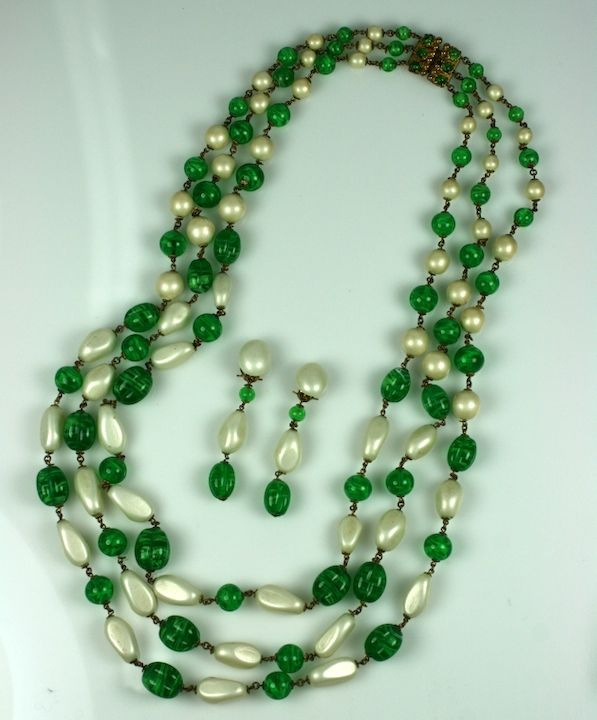Pearl and Emeralds. This elegant and classic combination takes on a different effect when supersized to this proportion. Chanel sticks to her established idioms and uses 3 strands of off-shaped and baroque pearls and beads for this massive sautoir