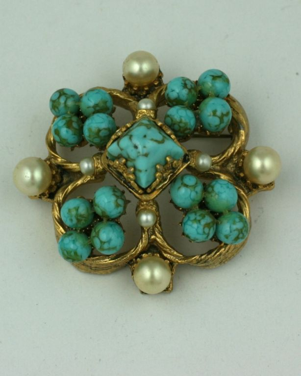 "Chanel renaissance style brooch quatrefoil in form of turquoise pate de verre and multiple pearls. This style of brooch was one of Chanel's ""Fords"" of bijoux fantasie made by Goossens in bronze with varied gem colors and configurations. 1950s"