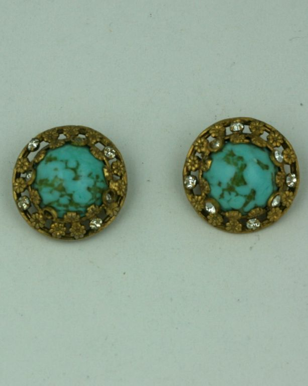 Chanel classic earclips of faux turquoise pate de verre cabochons set in gilt bronze floral filigree, hand set with pastes by studio Goossens. The style of these particular earclips are a staple in the Chanel oeuvre of her post war bijoux fantasie