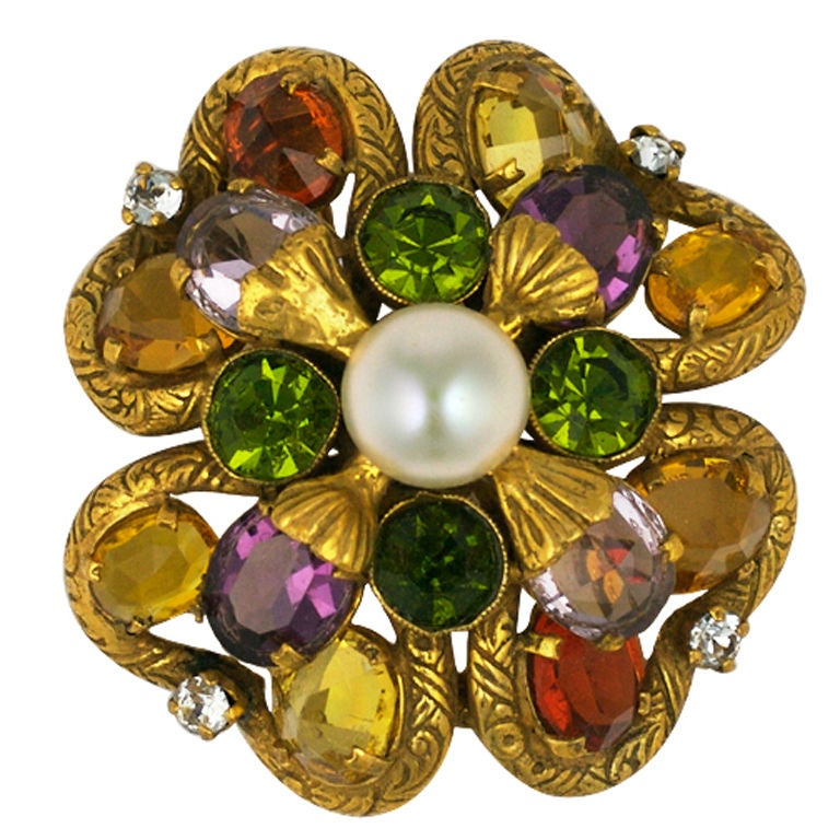 Coco Chanel's personal brooch in the form of a four leaf clover of gilt chased bronze set with a central raised faux pearl. The pearl is surrounded by amythest,citrine,olivine and deep amber colored pastes. The clover leaf's edges highlighted with