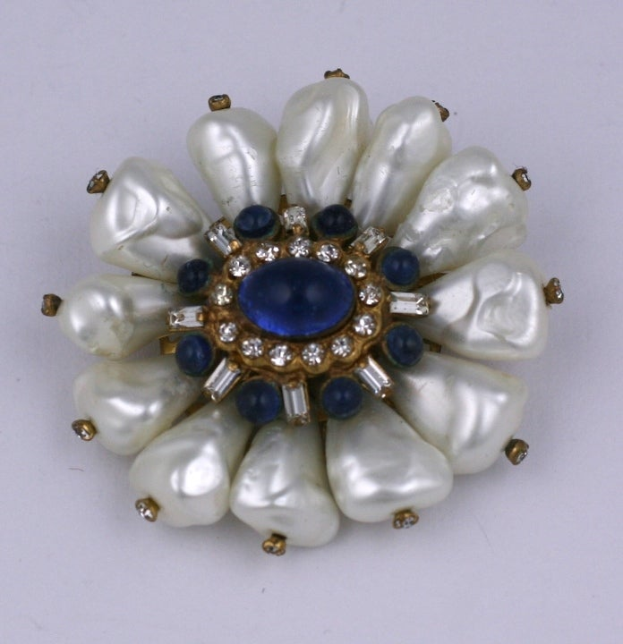 Chanel's sapphire poured glass, paste and dog tooth pearl brooch. The central motif, very classic in the Chanel iconography is mounted atop triangular hand made tooth pearls. Chanel was very fond of these irregular hand made pearls which mimicked