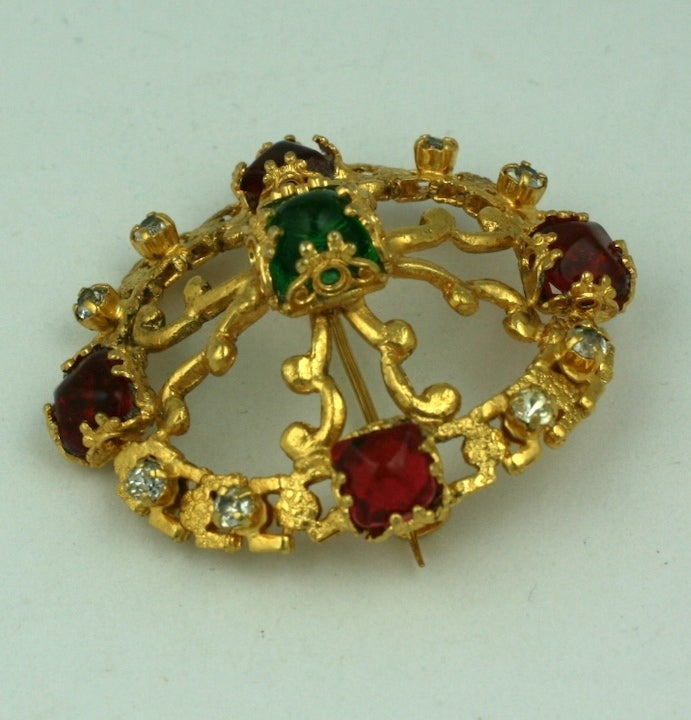 CoCo Chanel Renaissance style oval crest brooch in a modified quatrefoil form with signature cabochon emerald and ruby pate de verre stones and crystals. This type of brooch was one of Chanel's