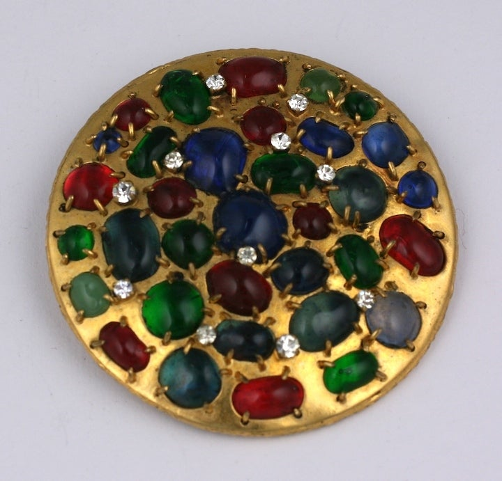 Chanel's Barbaric Byzantine round brooch of unusual and irregularly claw set poured glass emerald, ruby and sapphire irregular cabochons and prong set crystal strasses. This brooch is from the period when Chanel jewels were still made completely by