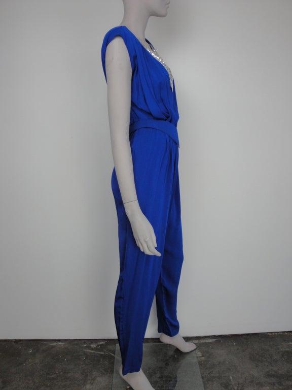 1980's cobalt blue jumpsuit with silver mesh neckline,shoulder pads and matching belt.
