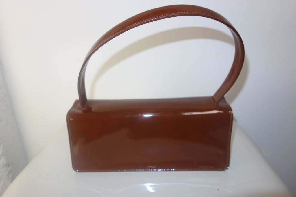 Tods brown patent leather handbag with one interior pocket.