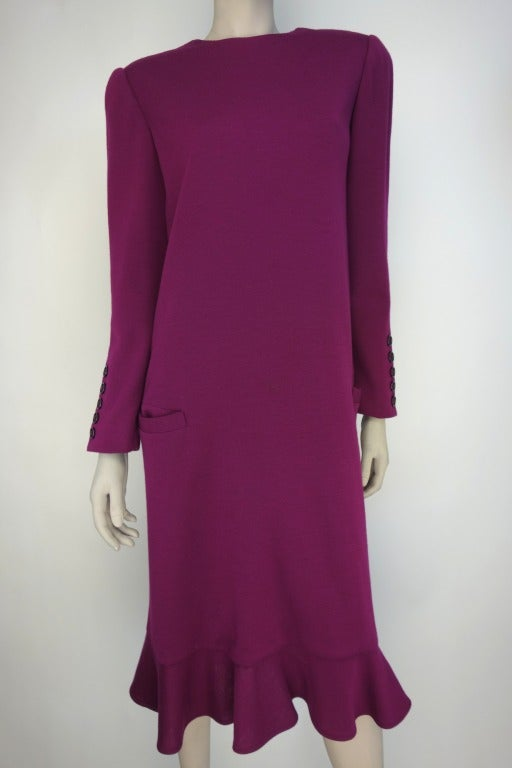 Bill Blass amethyst dress with button down back and sleeve button decoration, ruffled bottom, shoulder pads, and two front pockets.