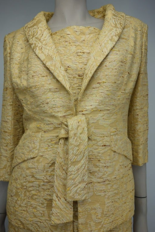 Pauline Trigere 1950s two piece ensemble with sleeveless dress and embellished button detail, fully lined in silk, and jacket with hook and eye clasp, two front pockets, and cotton velvet lining with 3/4 length sleeves.