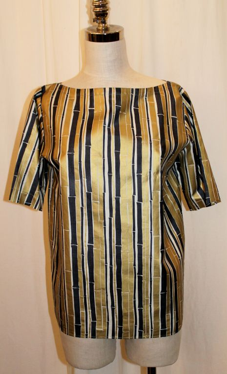 This YSL blouse has a gold and black bamboo print. The top is short sleeved with a shift look. It is in excellent vintage condition with light general wear. Size 38, circa 1990's.  Measurement Shoulder to Shoulder: 16 inches Sleeve length: 11 inches