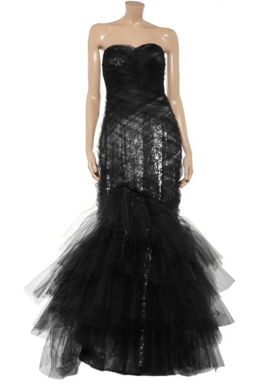 Black tie style is all about statement glamour, so make an entrance to remember in this sensational Marchesa gown. Lashings of jet-black tulle and showers of silver sequins combine to stunning effect, simply sweep up your hair to showcase the