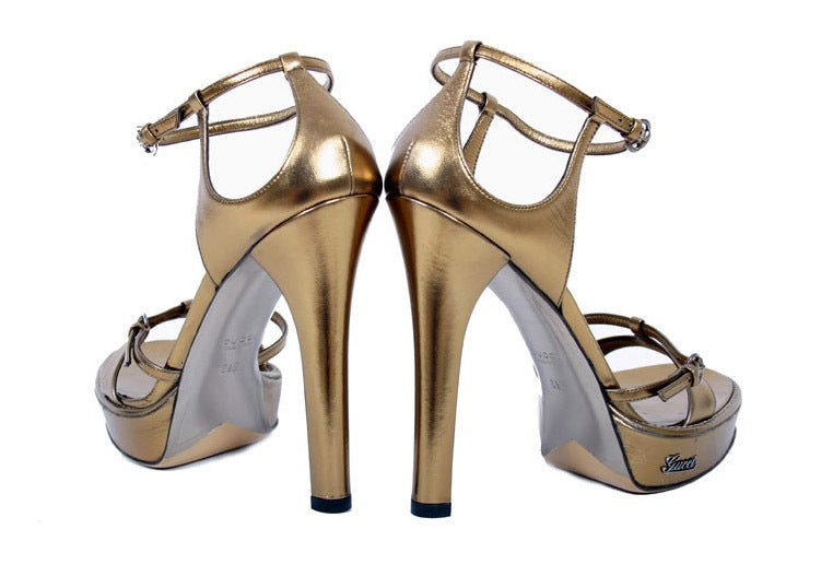 BRAND NEW GUCCI SHOES  New Gucci's sandal reaches new heights of show-stopping style in bronze metallic leather with elegant buckles and platform.   Color: Bronze metallic  Leather Leather lining and sole Heel measures approximately 5 1/4'' Platform