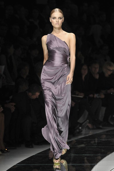 Make a grand entrance at your next black-tie event with a magnificent Versace dress. Styled with a one-shoulder neckline this purple, floor-length gown oozes sophistication. A ruched bodice hugs the waist before cascading to the floor. Sequin hearts