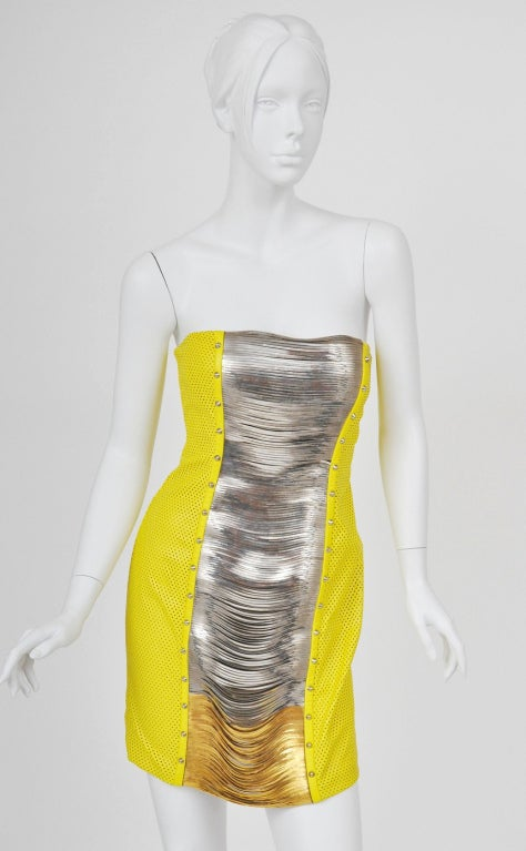 BRAND NEW VERSACE DRESS Illuminate your new season wardrobe with Versace's scene-stealing yellow leather mini dress with silver/gold woven metal panels on the front.  Perforated leather Fully lined with sheer nude mesh Inner corset  Size  42 - US