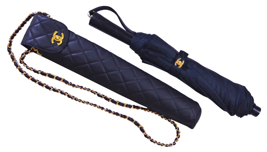 This is a fabulous vintage Chanel umbrella with case.  In mint condition, from the early 1980s. The case is waterproof material, coated in plastic.  The umbrella handle is quilted leather.