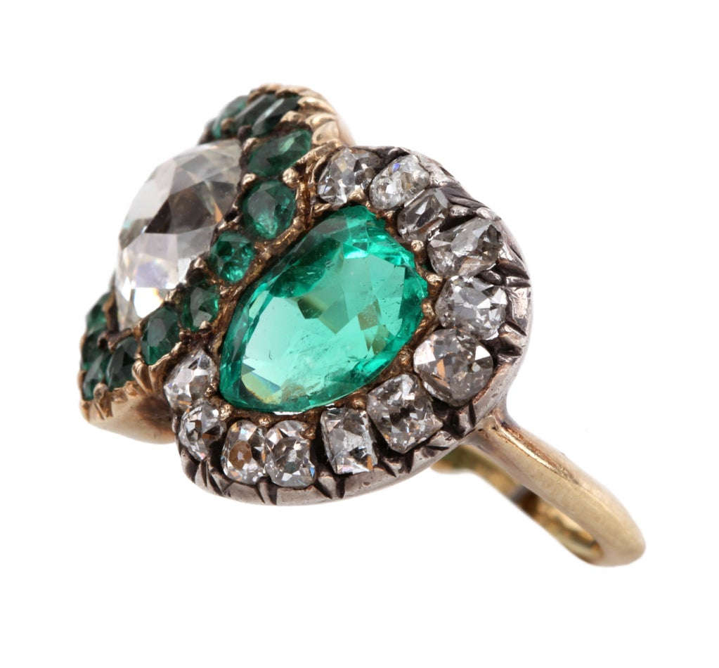 English twin heart ring with beautiful old cut diamonds and emeralds. Approximate 1.30 ct pear shaped diamond and 1.20 ct emerald. Silver and 15k gold. Size 5.5, can be sized.  Please see bellandbird.com for more of our rings.