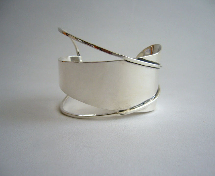 "A large sterling silver bracelet designed by Paul Lobel of New York.  Lobel had a studio and retail shop in New York's Greenwich Village in the 1940s and 1950s. His work has been included in museum exhibitions worldwide. Bracelet measures 2"" at its"