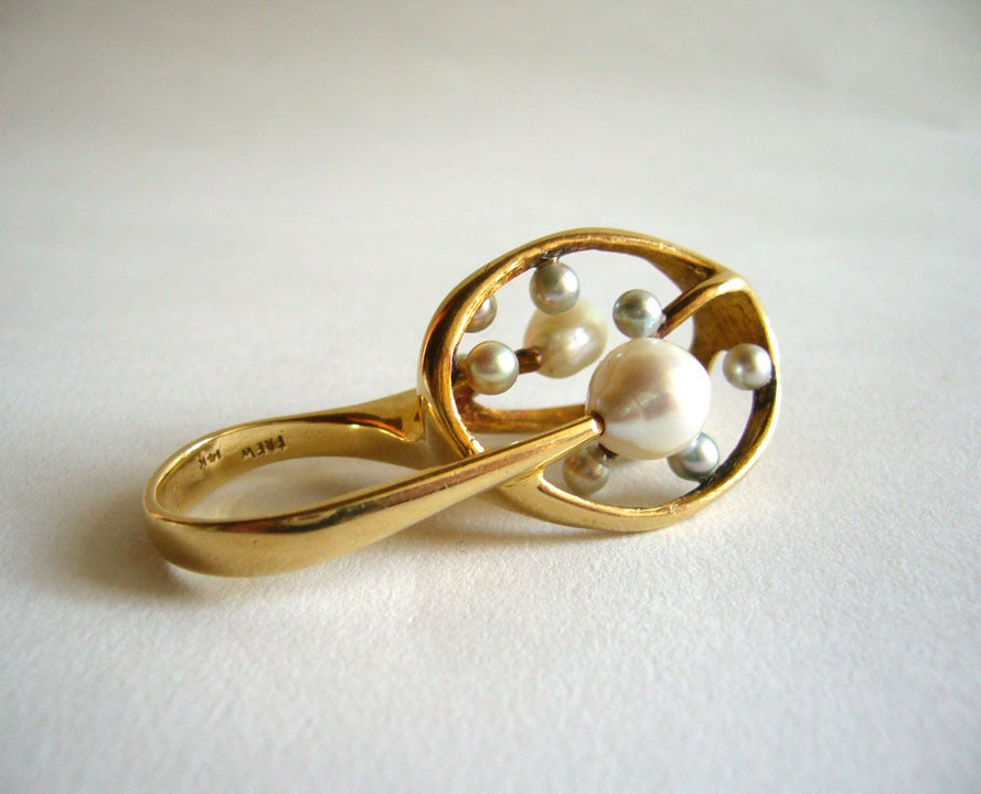A stunning 14k gold and pearl ring designed and created by J. Arnold Frew of Arcadia, California.  Ring is comprised of eleven white and grey pearls set within a 14k gold upright web.  The top of the ring stands 1 1/4