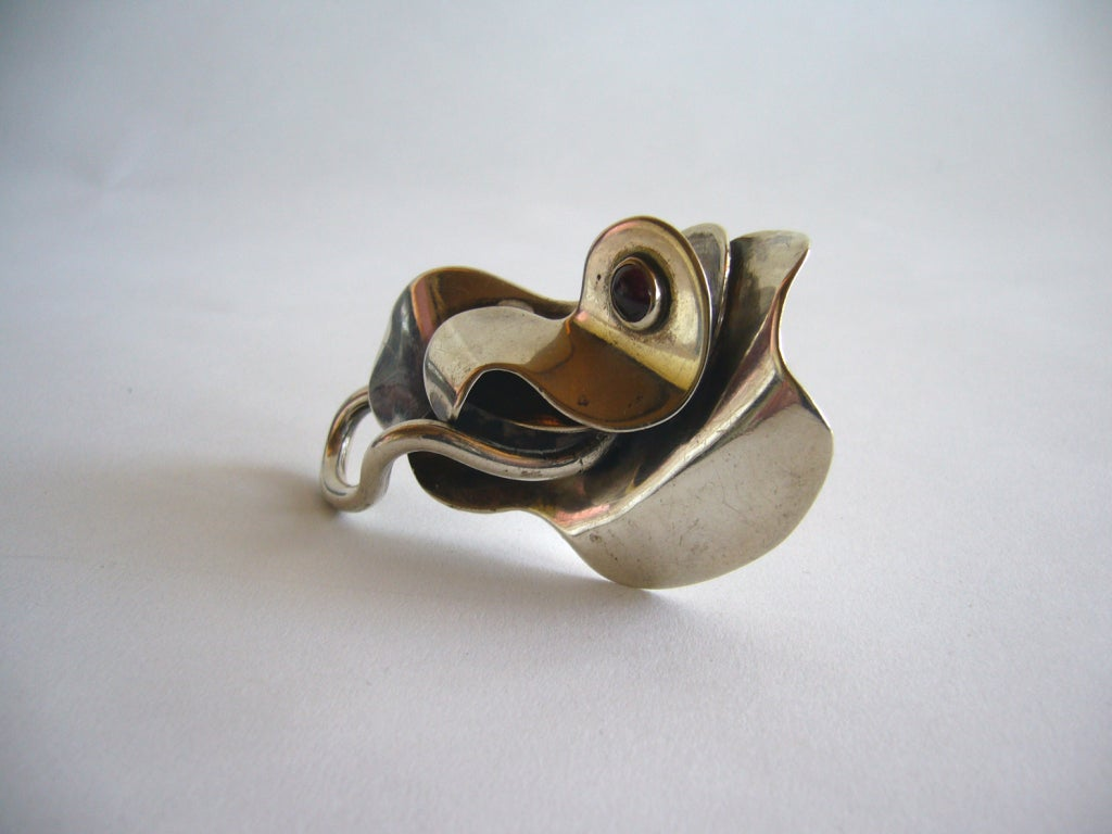 An early, rare multi-layered sterling and garnet brooch designed by Joan Hurst and Jill Kingsbury of New York City, New York.  This is a large example of their work and has surrealist influence as seen in works by Sam Kramer. The brooch measures 3