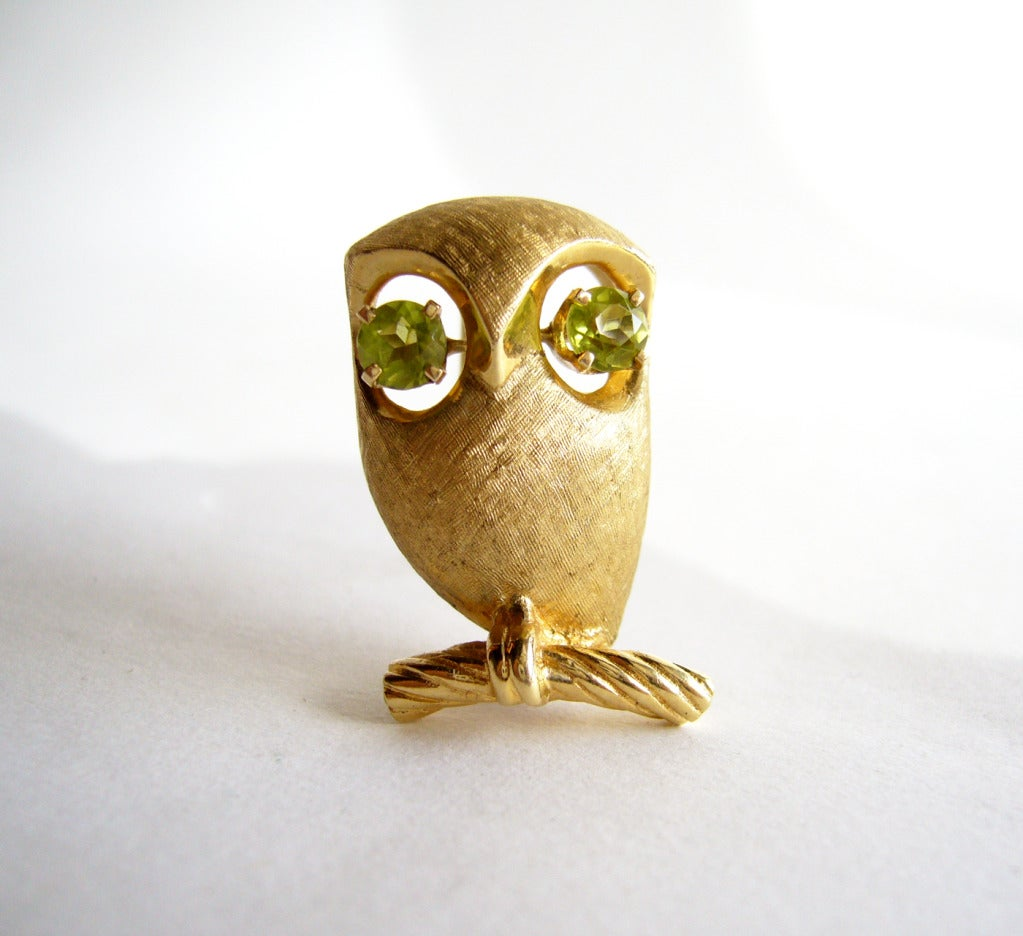 "A 14k gold owl on branch pin.  Owl features faceted peridot stones for its eyes.  Brooch measures 1"" in length by 5/8"" wide.  Signed 14k and in excellent vintage condition.  Total weight of 8 grams."