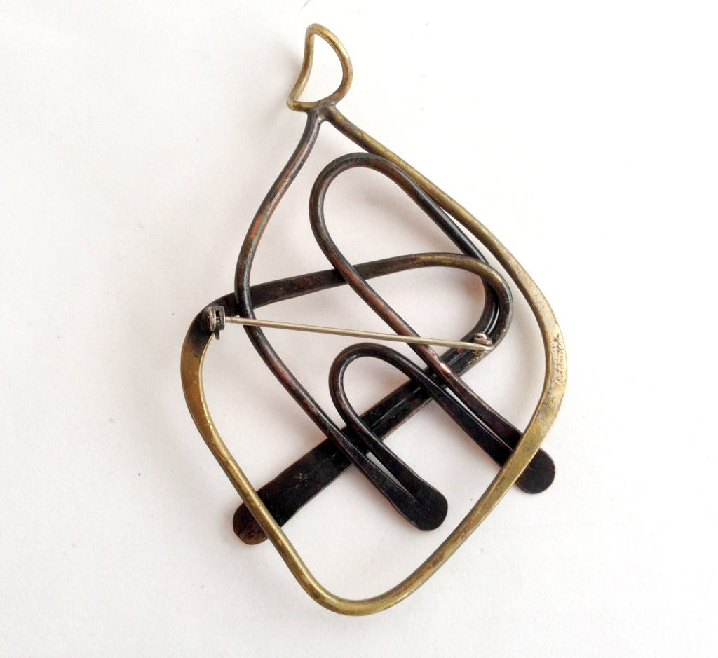 A large handmade copper and brass pendant or brooch of abstract form created by Art Smith of New York.  Pendant measures 4 1/4