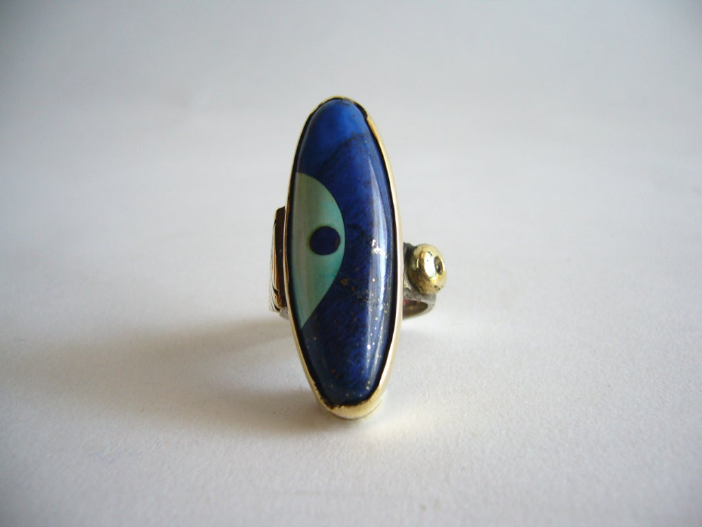A turquoise, lapis, sterling and 14k gold ring designed by Daniel Macchiarini of San Francisco, California.  Shank has cross hatching detail and the bezel is quite unique with a cut out in its design. Ring is a size 6 1/2 and is signed Macc. In very