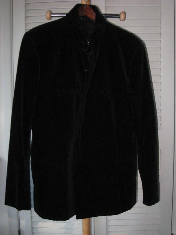 Vintage Thierry Mugler Men's Avantgarde Black Velvet Evening Suit with Snaps inside concealed instead of buttons. The high collar is closed with hooks. It has slits for all pockets, with Black Silk Lining. Pants have two silver buttons on the  back