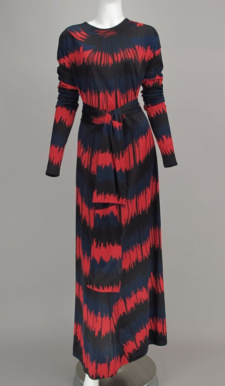 Dated 1977, Roberta di Camerino red, blue and black optical print silky knit maxi dress. Pull on style dress with jewel neckline, extra long sleeves each with three horizontal seams. A line dress with self tie belt. Unusual geometric optical print.