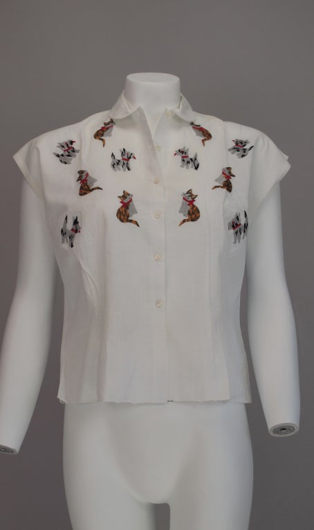 From the 1950s a charming hand made white handkerchief linen blouse, which is hand embroidered with perky cats and dogs...Custom made for the Cove shop which was located on Worth Ave. Palm Beach, Florida during the 1950s & 60s...Button front with