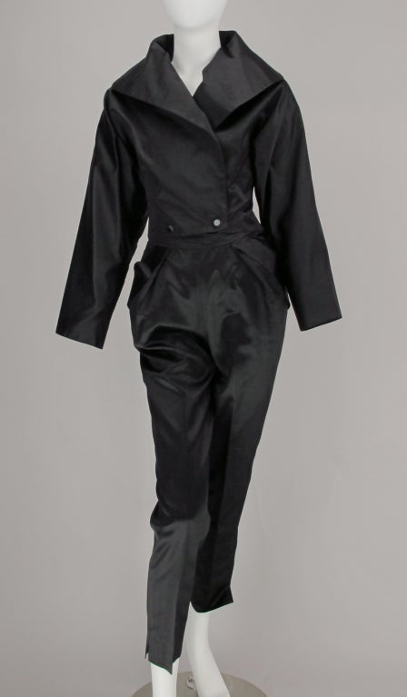 1980s Black silk satin pantsuit from Vicky Tiel…cropped bat-wing jacket with fitted waist that closes with two buttons, plunge neckline with shawl collar, jacket is fully lined…Ankle length pant with fitted waist band, two banded  hip front pockets,