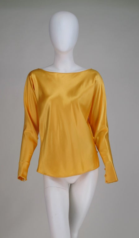 Gres Boutique saffron silk satin tunic blouse...Pull on style with bateau neckline, long dolman sleeves taper to loop and button cuffs, there are buttons and loops  at one hip side and a vent at the other, top  is fully lined in silk...Marked size