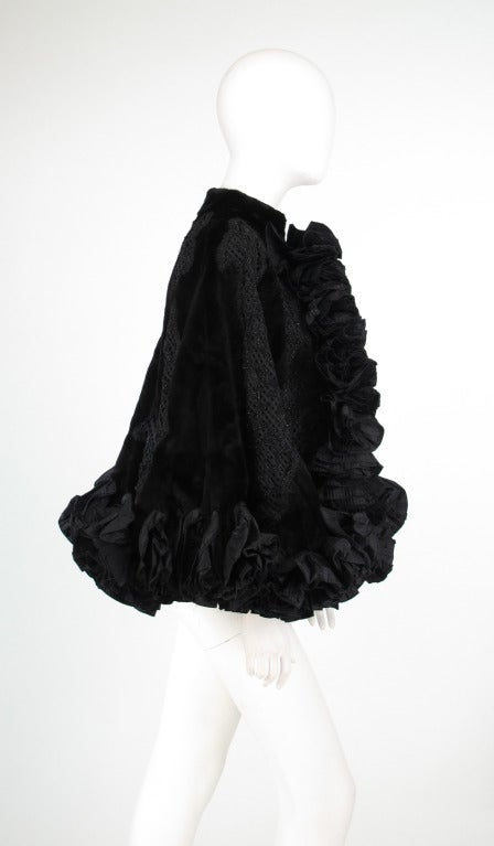 Evening drama from Oscar de la Renta, Couture...Victorian inspired evening cape of black sheared beaver with large diamond shape panels of decorative soutache braid and black faceted beaded panels...The hem and front facings are silk taffeta