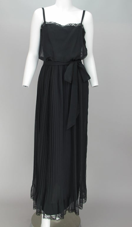 Fluttery chiffon that is great for dressing up with lots of great jewelry...Adele Simpson...Sheer black chiffon maxi dress from the late 1960s...camisole top with lace trim and fitted lining...attached maxi skirt is knife pleated and trimmed with