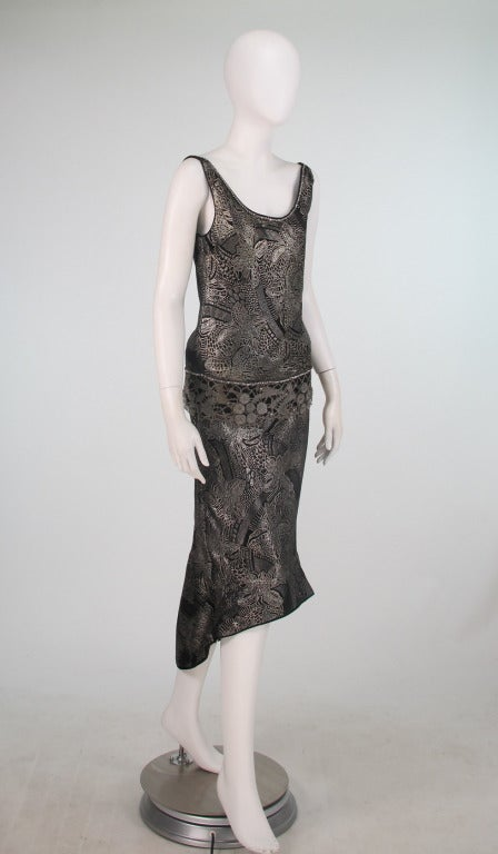 A fabulous example of the 1920s...Flapper dance dress...Silver metallic brocade, with metallic lace trim that is scattered with rhinestones, trimmed with prong set rhinestones at the neckline and hip...Bias cut this dress hugs the body...Low scoop