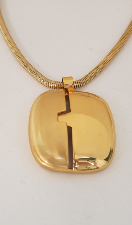 """1970s Lanvin gold modernist pendant necklace...Large pendant is matte gold on one side and bright gold on the other...With original gold snake chain...In excellent wearable condition...  Measurements are: Pendant 1 1/2"""" wide x 2"""" high Chain drop"""