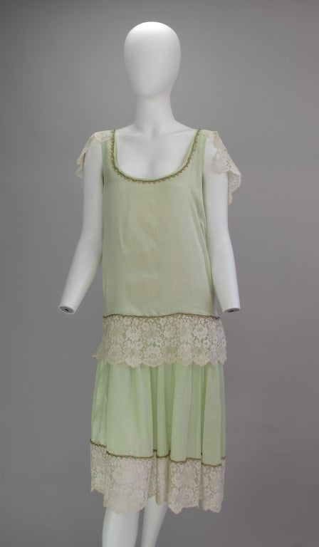 From the 1920â??s an amazing mint green silk flapper dress, trimmed with off white silk/cotton lace and fine silk floss and metallic thread braid. The dress features an over tunic with scoop neckline and deeper scooped back, side floating sleeves