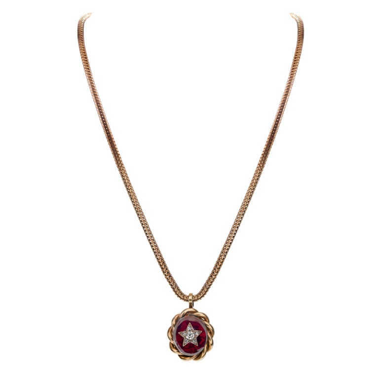 A lovely antique diamond and garnet pendant set in a handmade 15k yellow gold setting. The center diamond weighs 1/4 carat and is a old-mine-cut, encircled by five rose-cut diamonds. These stones are set in yellow gold, which is set on top of the