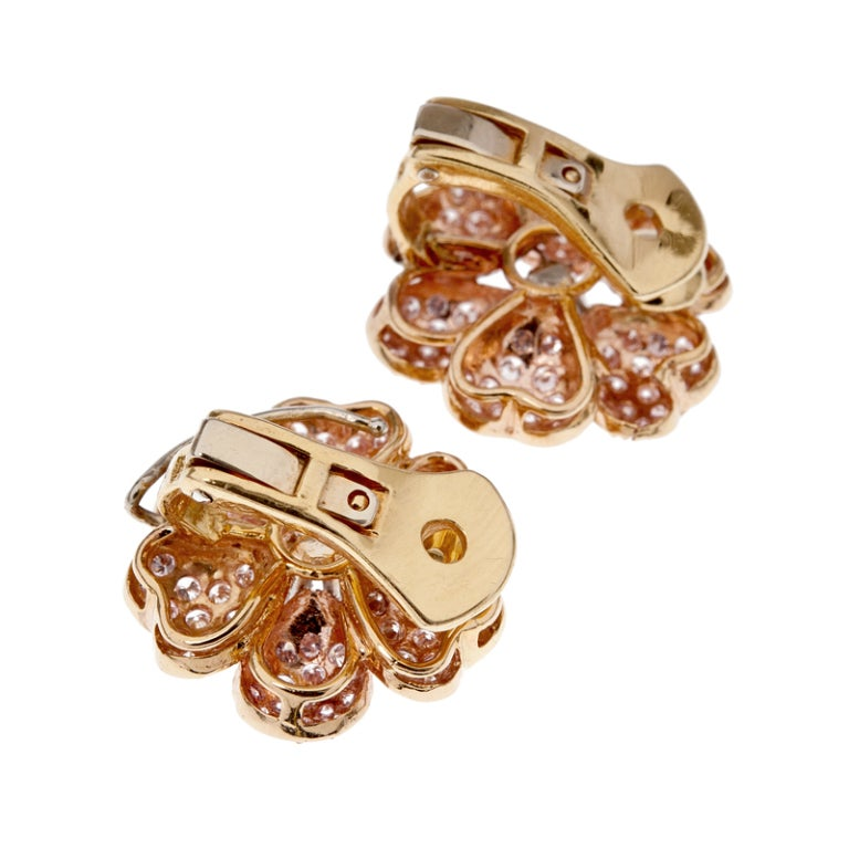 Fancy Pink Diamond Petals surround a center white diamond in these charming flower shaped earrings.  Eighteen karat yellow gold mountings embrace 3 carats of fancy pink diamonds that surround the center white diamonds which total .60 of a carat.
