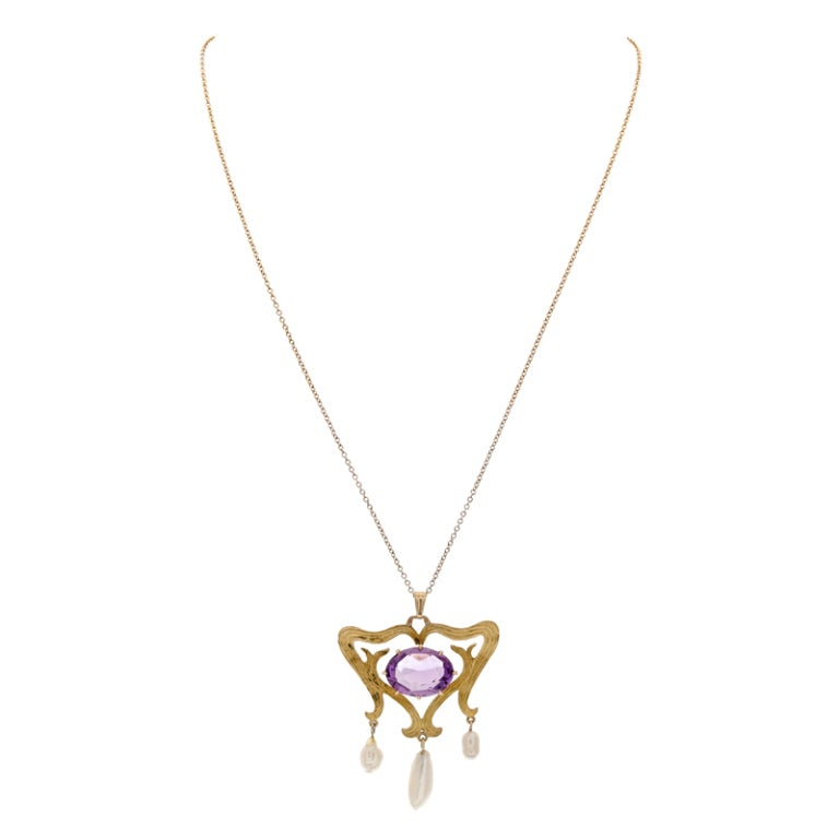 American organic beauty... crafted in 14 karat yellow gold and designed as textured branches, sweeping past each other to their glory. Baroque pearls and amethyst compliment the hand created strokes of gold. Pendant created circa 1895. Suspended